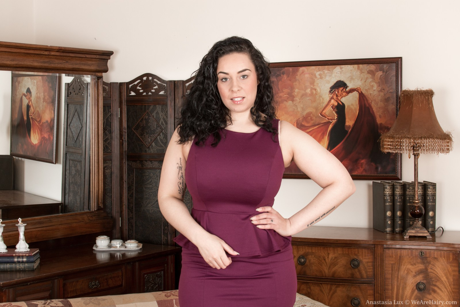 Huge-titted Anastasia Lux strips undressed in the living room and gives us a look at her curly bod